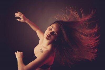Fototapeta Młoda brunetka kobieta tańczy i włosy płynący w powietrzu