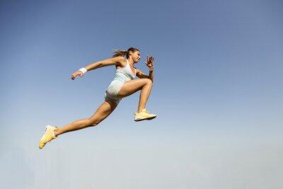 Fototapeta Młoda kobieta, biorąc skok w dal