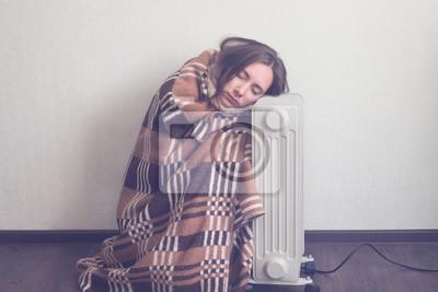 Fototapeta Młoda kobieta w wełnianej kratę rozgrzewkę rąk nad grzałką elektryczną