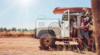 Fototapeta Młoda para na podróż do czytania mapy na kierunkach