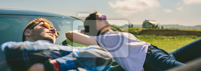 Fototapeta Młoda para odpoczynku leżącego na przedniej szybie i masce samochodu