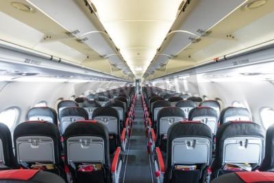 Fototapeta Modern interior of aircraft. Black and red seats inside airplane. Symmetric vanishing row of seats inside air transport. Economy class of flight. Equipment for travelling. Empty illuminated plane.