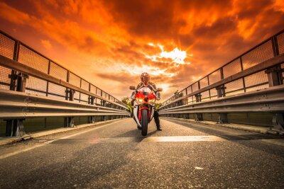 Fototapeta Moto da strada pronta alla partenza sotto un cielo rosso al tramonto
