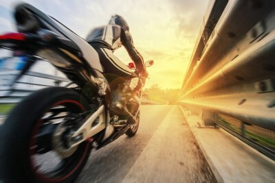 Fototapeta Moto da strada sfreccia vicino al reling al tramonto
