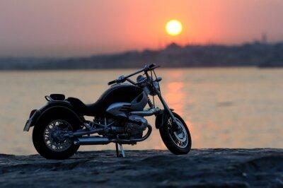 Fototapeta Motocykl na skałach w zachód słońca i złote godzin