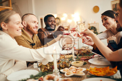 Fototapeta Multi-ethnic group of people raising glasses sitting at beautiful dinner table celebrating Christmas with friends and family, copy space