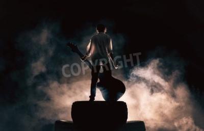 Fototapeta Muzyk gra na dużym gitara rock w wielkim dymie