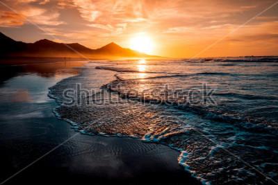 Fototapeta Niesamowity zachód słońca na plaży z niekończącym się horyzontem i samotnymi postaciami w oddali oraz niesamowitymi spienionymi falami. Wulkaniczne wzgórza w tle w idyllicznych ciepłych barwach.