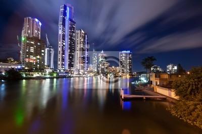Fototapeta Nowoczesne miasto w nocy z chmur przemieszczających