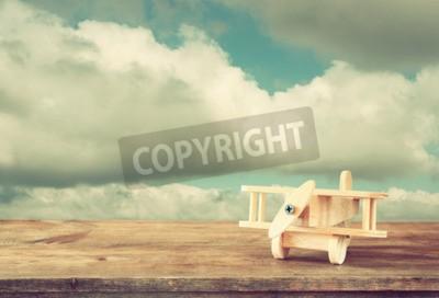 Fototapeta Obraz drewniane zabawki samolot nad drewnianym stole przeciwko pochmurne niebo. Obraz stylu retro