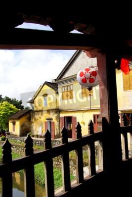Fototapeta Old yellow house, seen from  inside the Japanese Covered Bridge,  Hoi An, Vietnam