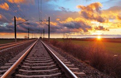 Fototapeta Orange sunset in low clouds over railroad