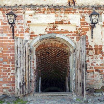 Fototapeta Otwarte wyblakły drewniane drzwi prowadzące do lochu starego zamku