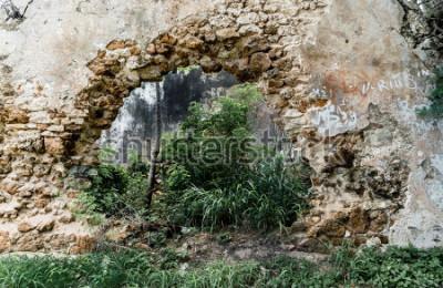 Fototapeta Otwarty w ścianie opuszczonego budynku z kamienia.