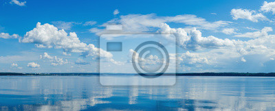 Fototapeta Panorama of calm lake, Kama river blue sky with clouds reflected in the water.
