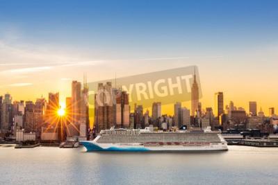 Fototapeta Panoramę Nowego Jorku na wschodzie słońca, jak widać z Weehawken, wzdłuż 42 ulicy kanion. Duży statek wycieczkowy pływa po rzece Hudson, podczas gdy promienie słońca rozciągają się między wieżowcami.