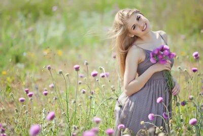 Fototapeta Piękna kobieta z bukietem kwiatów w polu