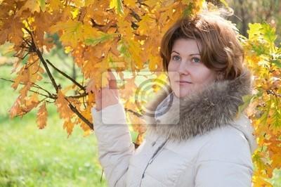 Fototapeta Piękna młoda kobieta w parku jesienią z liści
