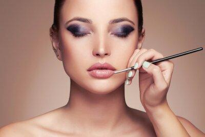 Fototapeta Piękna twarz kobiety. piękna dziewczyna z doskonałej make-up.Makeup artysty odnosi lipstick.cosmetics