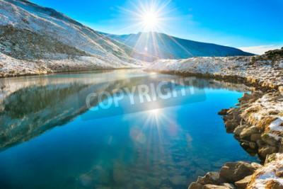 Fototapeta Piękne niebieskie jezioro w górach, w czasie sunrise rano. Krajobraz z śniegu świecącym słońcu