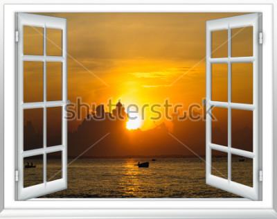 Fototapeta piękny zachód słońca nad widokiem na morze z okna z otwartymi zasłonami