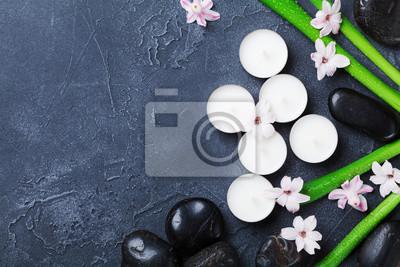Piękny zdrój tło z masażu otoczakiem, zielonymi liśćmi, kwiatami i świeczkami na czarnym kamienia stole od above ,. Aromaterapia, piękno, relaks i zen jak koncepcja.
