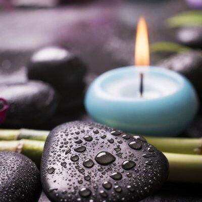 Fototapeta Pietra nera con gocce d'acqua w primo piano e candela sullo sfondo, makro