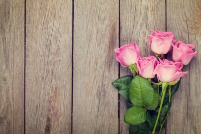 Fototapeta Pink roses bouquet over wooden table