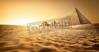 Fototapeta Piramidy egipskie w piaszczystej pustyni i jasne niebo