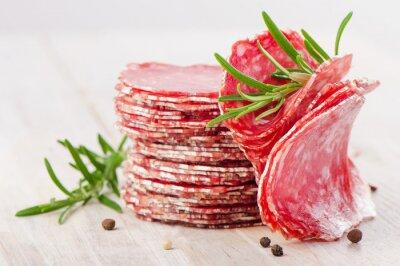 Fototapeta Plasterki kiełbasy salami na drewnianym stole.