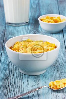 Płatki kukurydziane z rodzynkami i mleka w kubku ceramicznym