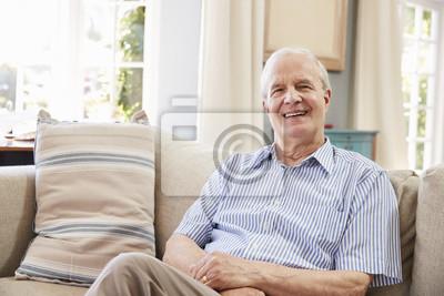 Fototapeta Portret uśmiechnięty starszego mężczyzna obsiadanie Na kanapie W Domu