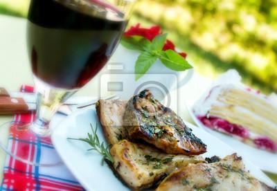 Fototapeta Posiłek na stole - ryby, czerwone wino i deser