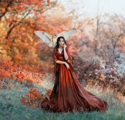 Fototapeta pretty young girl with black hair in cold forest, orange foliage of trees, fairy of autumn season in long red burgundy vintage dress with chic train, lady with white owl on shoulder, bloody sorceress