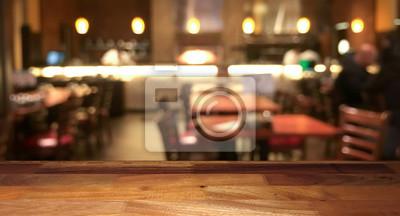 Fototapeta Pusty drewniany stół góry z rozmytych restauracji na tle