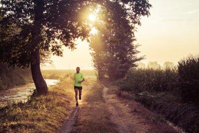 Fototapeta Ragazzo che corre all'alba su strada di campagna in estate