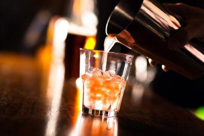 Fototapeta Ręce barman leje napój do szklanki