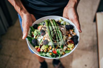 Fototapeta Ręce mężczyzny trzyma dużą głęboką talerz pełen zdrowych sałatek wegetariańskich paleo wykonanych ze świeżych ekologicznych ingridients biologicznych, warzyw i owoców, jagód i innych składników odżywc