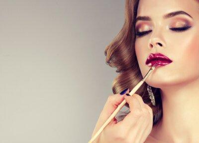 Fototapeta Ręka mistrza makijaż, malując usta młodej pięknej modelu. Makijaż w toku.