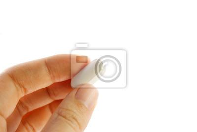 Fototapeta Ręka trzyma białą tabletkę na białym tle