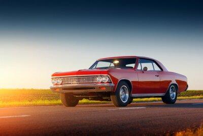 Fototapeta Retro czerwony samochód pobyt na drodze asfaltowej o zachodzie słońca