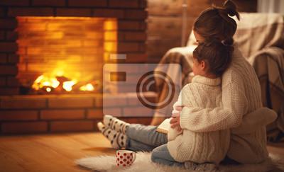 Fototapeta rodzina matka i dziecko przytula i ciepło w zimowy wieczór przy kominku.