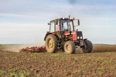 Fototapeta Rolnik uprawiający ziemię orną przed wysiewu