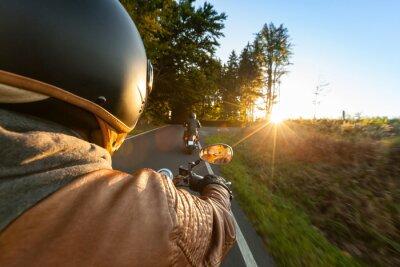 Fototapeta Rowerzysta jazdy motocyklem w słoneczny poranek