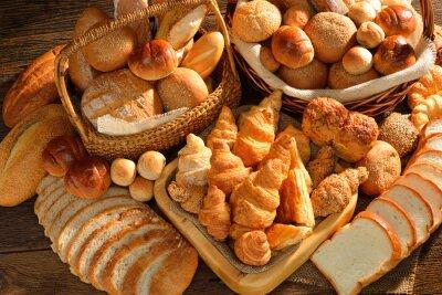 Fototapeta Różnorodność chleba w wiklinowym koszu na starym drewnianym tle.