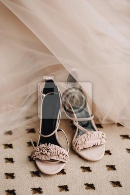 d267d54c Fototapeta Różowe eleganckie buty sandałów panny młodej na podłodze obok  sukni ślubnej. Przygotowanie do ślubu