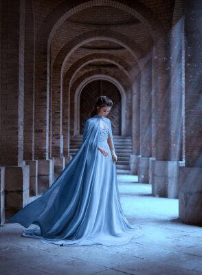 Fototapeta Sad Snow Queen walks in old castle. blue silk long raincoat train flying motion. Elven hairstyle cute face. Vintage fantasy art retro style. Frozen Fabulous woman photo shoot. sun magic shine rays