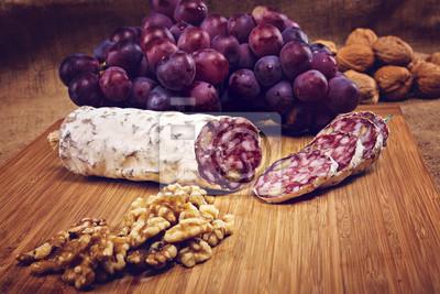 Fototapeta salami z orzechami na drewnianym talerzu z winogron