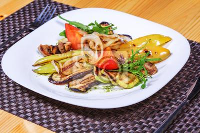 Fototapeta Sałatka z grillowanymi warzywami na białym talerzu udekorowane ziołami