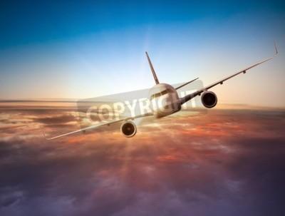 Fototapeta samolot komercyjny latania nad chmurami w dramatycznym świetle słońca